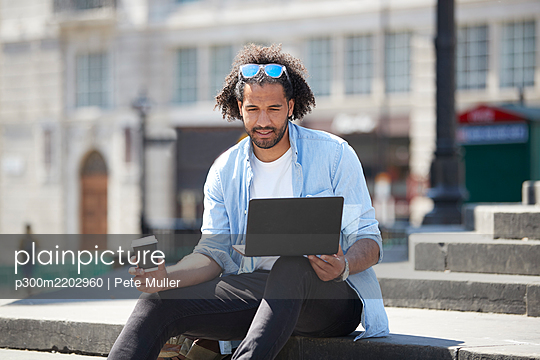 Portrait of young man with coffee to go sitting on stairs outdoors looking at laptop, London, UK - p300m2202960 by Pete Muller