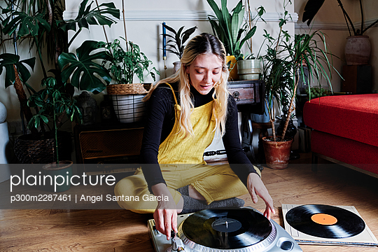 Smiling woman playing record on turntable at home - p300m2287461 by Angel Santana Garcia