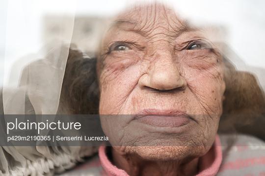 Old woman looking through window during Corona virus quarantine. - p429m2190365 by Senserini Lucrezia