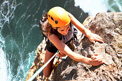 Focused female rock climber hanging from rock above ocean - p1023m1561180 by Trevor Adeline