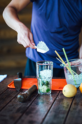 Barman prepares fruit alcohol cocktail based on lime, mint, oran - p1166m2094704 by Cavan Images