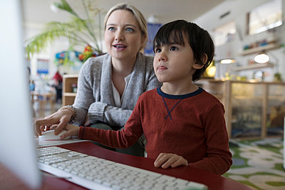 Preschool teacher and boy student at computer - p1192m1560146 by Hero Images