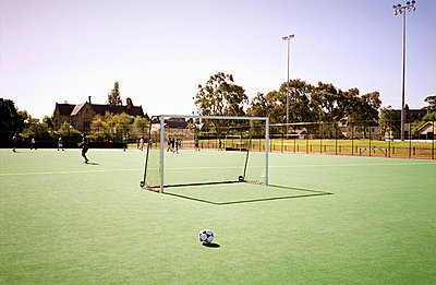 Soccer ball on soccer field with people training in background - p3013777f by Tobias Titz