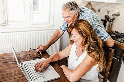 Older couple using laptop in kitchen - p429m659765f by Dan Brownsword
