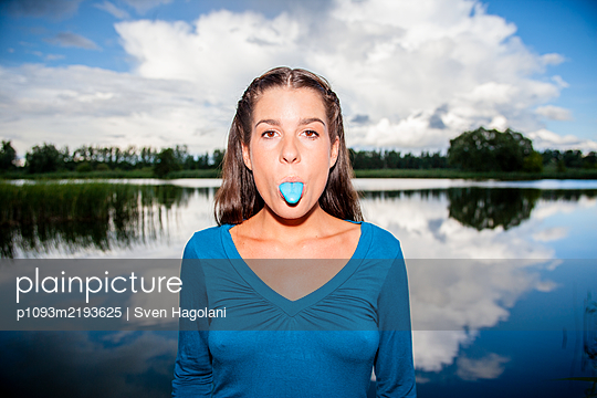 Young woman snaps her chewing gum on the lakefront - p1093m2193625 by Sven Hagolani