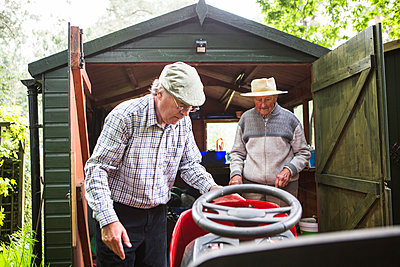 Senior men looking at lawn mower - p1026m1164176 by Patrick Frost