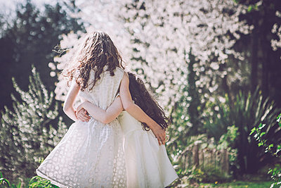Two girls in garden embracing  - p1150m1041243 by Elise Ortiou Campion