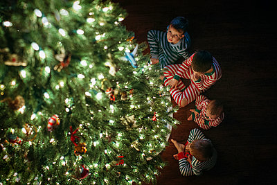 High angle view of siblings sitting by Christmas tree at home - p1166m1403024 by Cavan Images