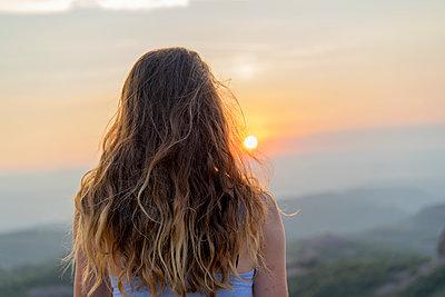 Woman watching sunset in the mountains - p300m2028682 von VITTA GALLERY