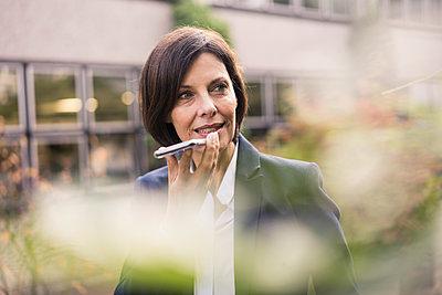 Mature businesswoman sending voicemail through smart phone at office park - p300m2266553 by Joseffson
