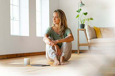 Blond woman day dreaming while sitting by digital tablet and coffee mug on floor in living room - p300m2277508 by Steve Brookland