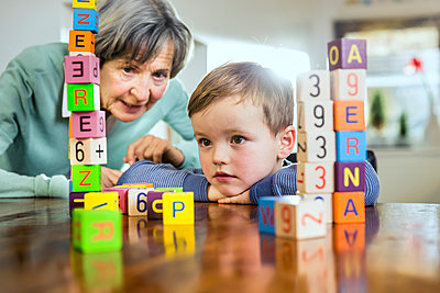 Senior woman and boy looking at toy block stack on table - p300m2287423 by Stefanie Aumiller