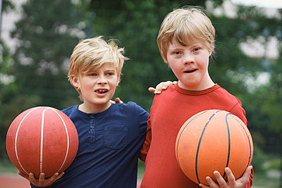 Brothers standing arms around while holding basketballs in park - p301m1180563 by Halfdark
