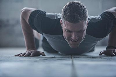 Caucasian athlete doing push-ups on floor - p555m1411991 by John Fedele