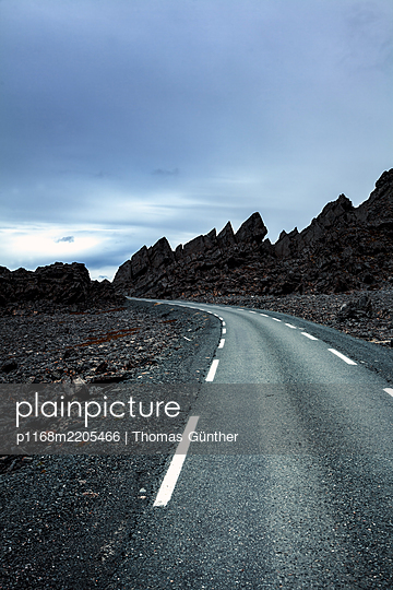 Country road in barren land rocky andscape - p1168m2205466 by Thomas Günther