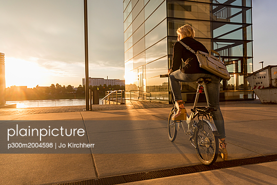 Senior woman with city bike at the riverside at sunset - p300m2004598 von Jo Kirchherr
