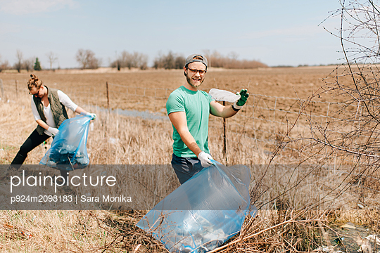 Couple picking up rubbish by field, Georgetown, Canada - p924m2098183 by Sara Monika