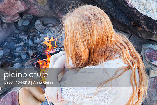 Girl sitting by fire - p956m1044213 by Anna Quinn