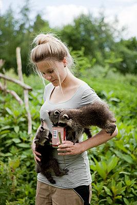 Junge Frau mit drei Waschbären - p1195m1112995 von Kathrin Brunnhofer
