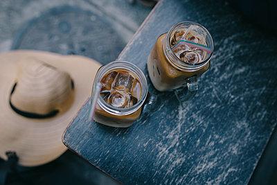 Gläser mit Eiskaffee und Eiswürfeln auf blauem Tisch - p1497m1585962 von Sascha Jacoby