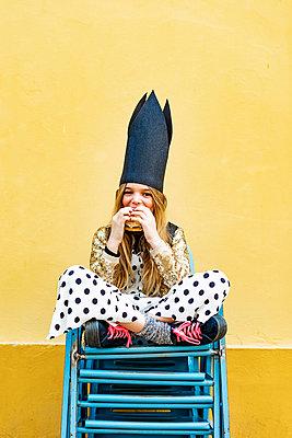 Portrait of girl wearing black crown sitting on stack of chairs eating Hamburger - p300m2102977 von Eloisa Ramos