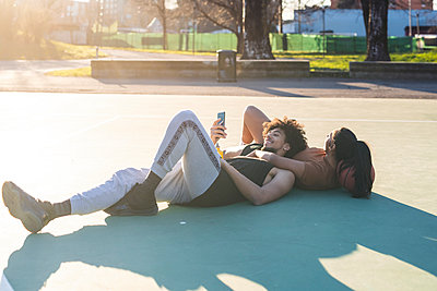 Sportive young couple taking a break lying on basketball court - p300m2171160 by Eugenio Marongiu