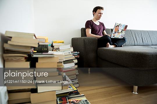 Junger Mann mit Laptop und Büchern - p1221m1150124 von Frank Lothar Lange