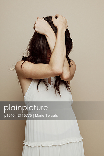 Caucasian girl in white dress hiding her face - p1540m2115775 by Marie Tercafs