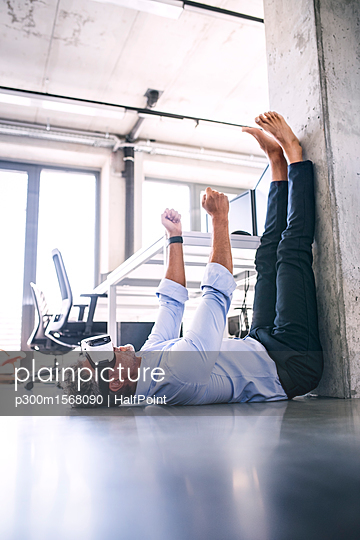 Barefoot mature businessman lying on floor in office wearing VR glasses - p300m1568090 by HalfPoint