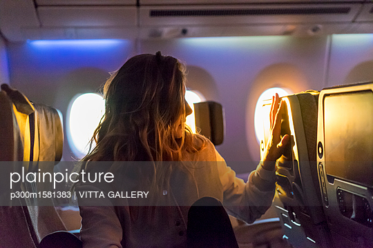 Young woman in plane at sunrise - p300m1581383 von VITTA GALLERY