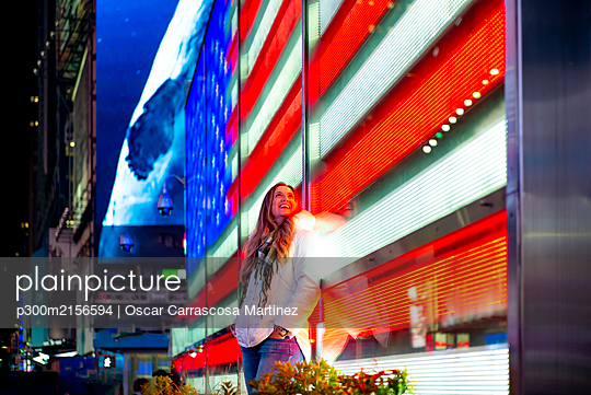 USA, New York, New York City, Portrait of young beautiful woman leaning on Times Square LED display at night - p300m2156594 by Oscar Carrascosa Martinez