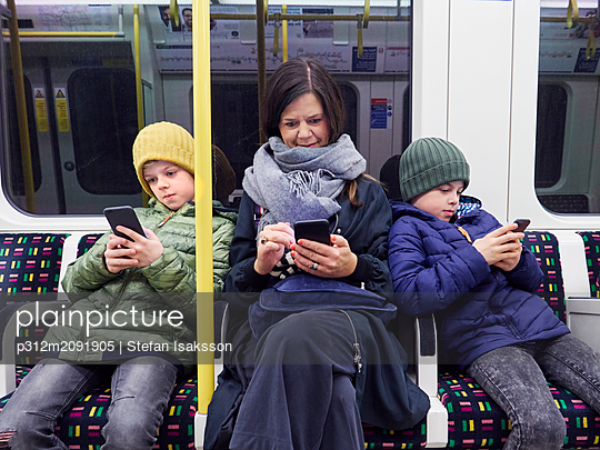 Mother and son using cell phones in subway train - p312m2091905 by Stefan Isaksson