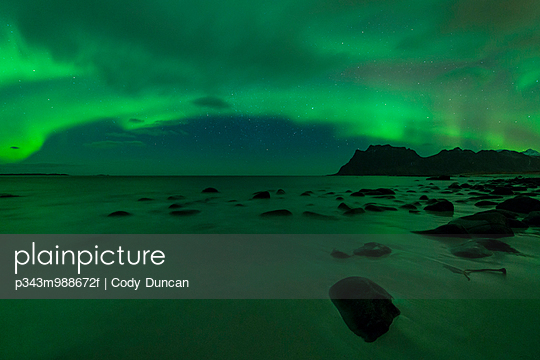 Northern Lights - Aurora Borealis shine in Sky over Uttakleiv beach, Vestvågøy, Lofoten Islands, Norway - p343m988672f by Cody Duncan