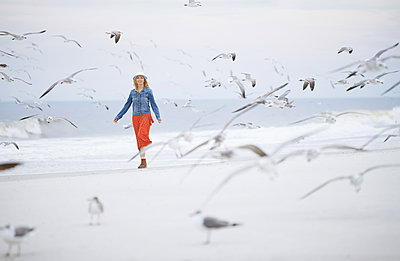 Woman walking next to the ocean surrounded by flying seagulls - p1577m2150308 by zhenikeyev