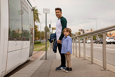 Smiling father and son hand in hand at tram stop in the city - p300m2070408 von Mauro Grigollo