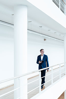 Smiling senior male entrepreneur with digital tablet looking away while walking in office corridor - p300m2265731 by Gustafsson