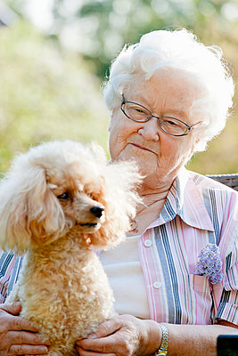 Senior woman holding dog - p312m1551892 by Johner Images