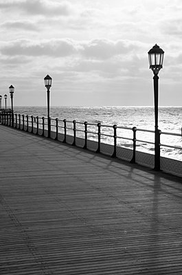 Lamp posts along deserted Worthing Pier boardwalk with the sea in the background - p3313108 by Gail Symes