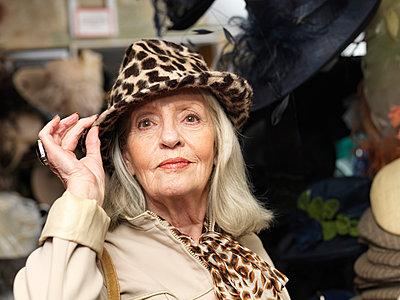 Glamorous senior woman in leopardskin hat - p429m895365f by Colin Hawkins
