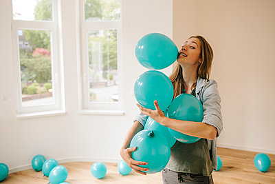 Young woman in new apartment playing with balloons - p586m1064903 by Kniel Synnatzschke
