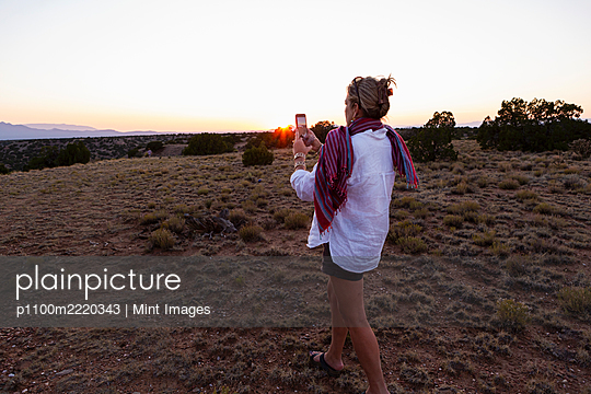 adult woman photographing sunset on her smart phone. - p1100m2220343 by Mint Images