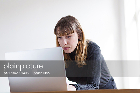 Young woman working on laptop - p1301m2021405 by Delia Baum