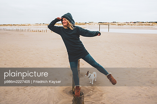 Germany, Schleswig-Holstein, Sankt Peter-Ording, Woman and dog on the beach - p986m2227405 by Friedrich Kayser