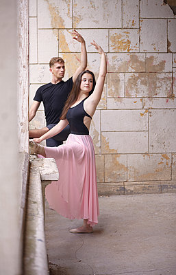 Friends with arms raised practicing ballet in old building against wall - p1166m2024730 by Cavan Images