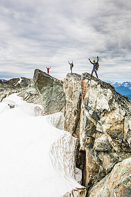 Three climbers stand on a rocky summit with arms raised in the air - p1166m2162488 by Cavan Images