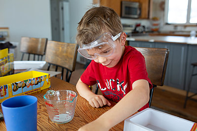 Child making funny face while conducting science experiment - p1166m2269671 by Cavan Images
