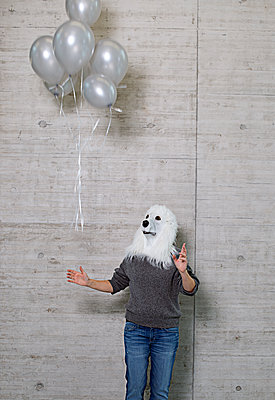 Person with dog mask lets go of balloons - p1366m2260591 by anne schubert