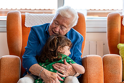 Grandmother hugging her granddaughter in living room - p300m2140358 by Gemma Ferrando