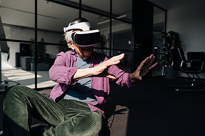 Senior businessman gesturing while using virtual reality headset sitting in office - p300m2252258 by Gustafsson