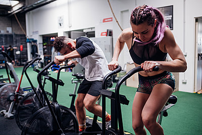 Young woman and man training together on gym exercise bikes, action - p429m2098424 by Eugenio Marongiu